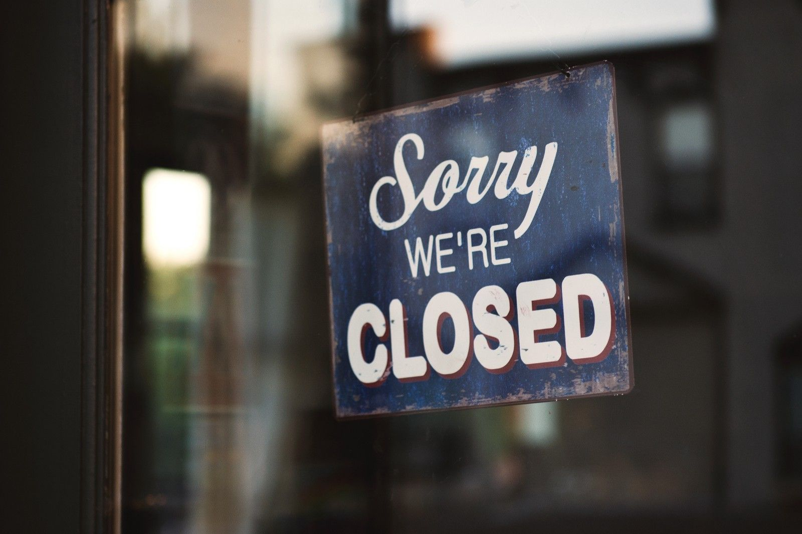 """close up of a sign that says """"Sorry we're closed"""" hanging in a window"""