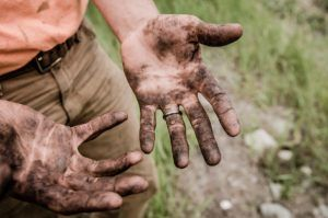 overhead view of a mans hands caked in dirt