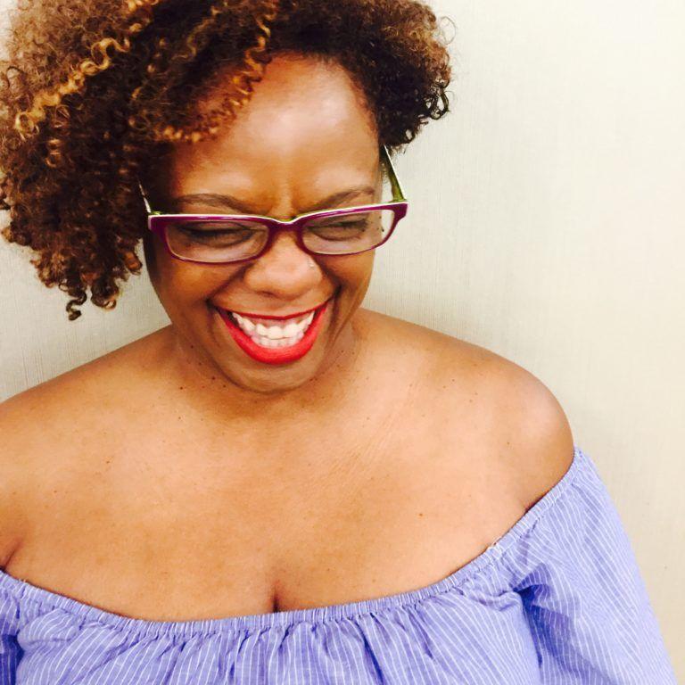 Portrait of Kim Crayton smiling wearing a purple blouse and purple glasses