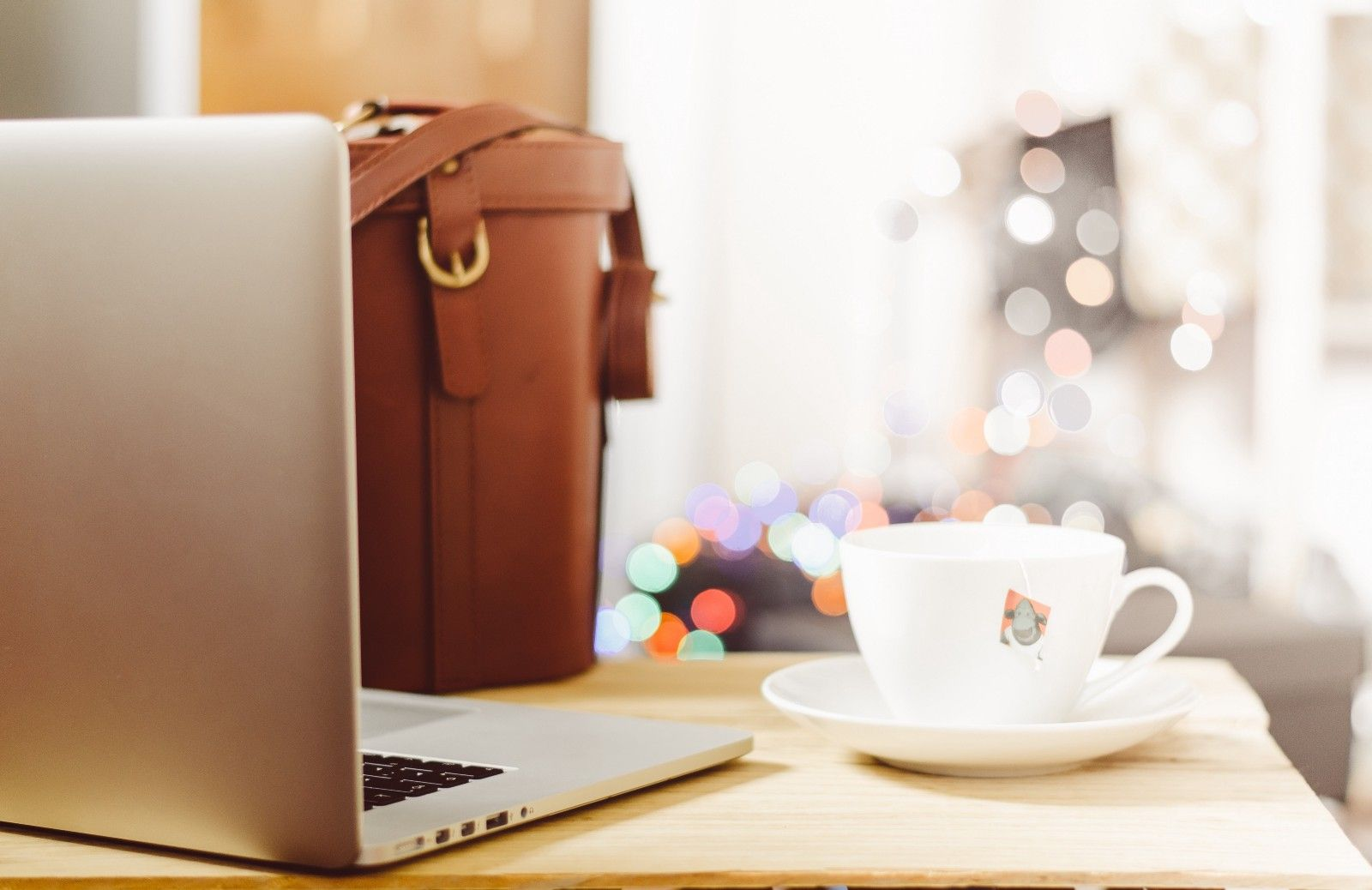 A laptop facing away from the foreground and cup of tea sitting side by side on a table with a workbag in the background.