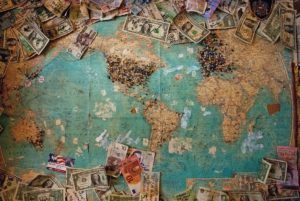 Overhead view of a world map with many us dollar bills strewn across the top and bottom edges