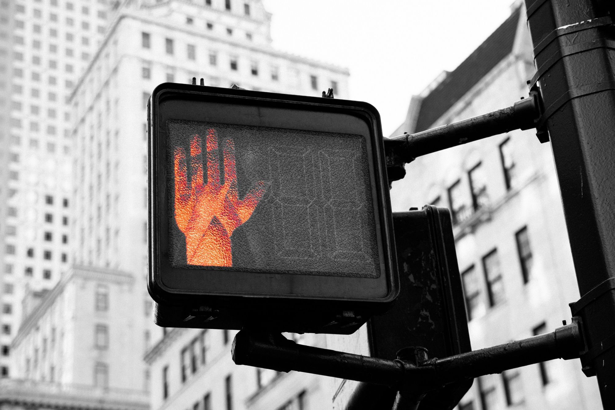 United states black and white photo of a pedestrian signal white the stop hand signal colored orange