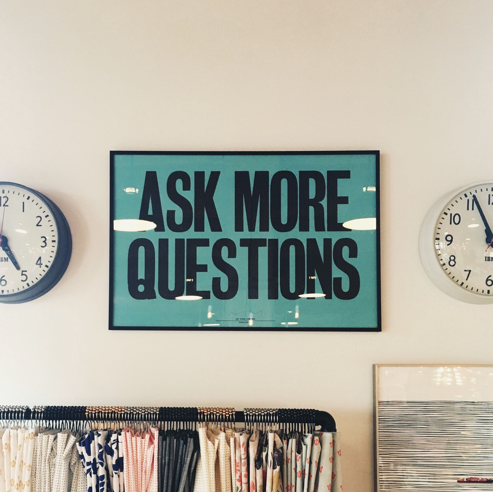 """A teal colored graphic poster with the text """"Ask More Questions"""" hanging on a beige wall between two IBM branded clocks"""